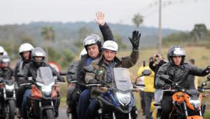 """Presidente Jair Bolsonaro em cima de moto com o prefeito de Chapecó. Eles usam capacetes e fazem um sinal de """"oi"""" com as mãos. Nos dois lados, outras motos em fileiras com pilotos."""