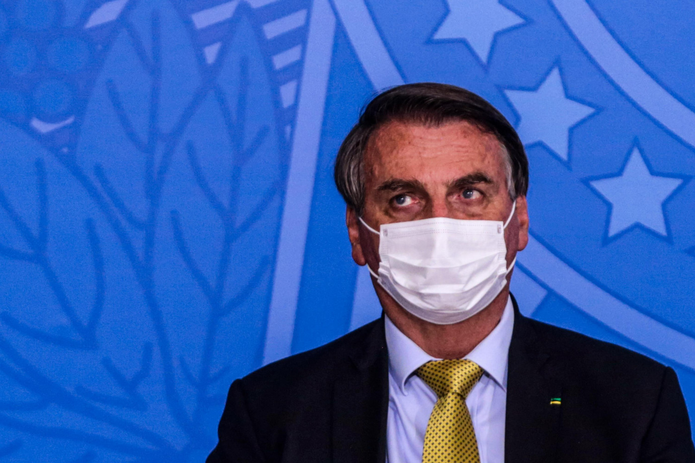 O presidente da república, Jair Bolsonaro, usa terno preto, gravata verde e camisa e máscara branca