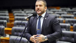 De terno preto, camisa branca, gravata xadrez (puxando para o azul), o deputado federal Carlos Jordy entrelaça as mãos enquanto fala no plenário da Câmara
