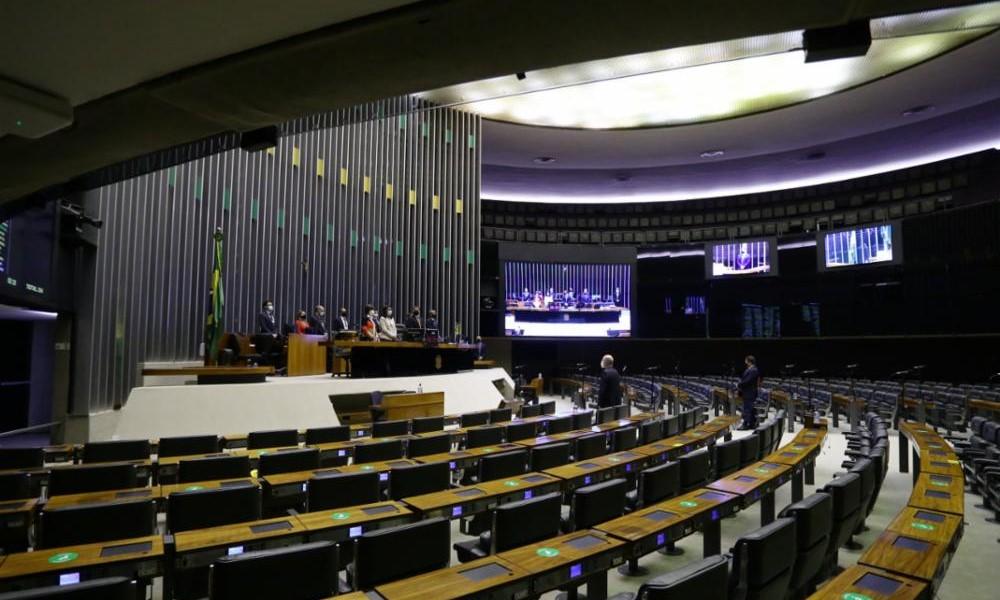 Plemário da Câmara dos Deputados vista a partir do lado esquerdo, com os bancos vazios e dois deputados em pé (além de outros oito em pé na mesa diretiva)
