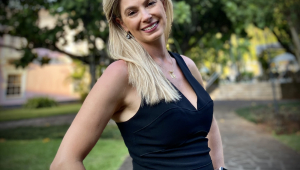 Mulher loira e branca de cabelos compridos, com as mãos apoiadas nos quadris e usando um vestido preto. Ela sorri para a câmera e faz uma pose com o corpo virado de lado.