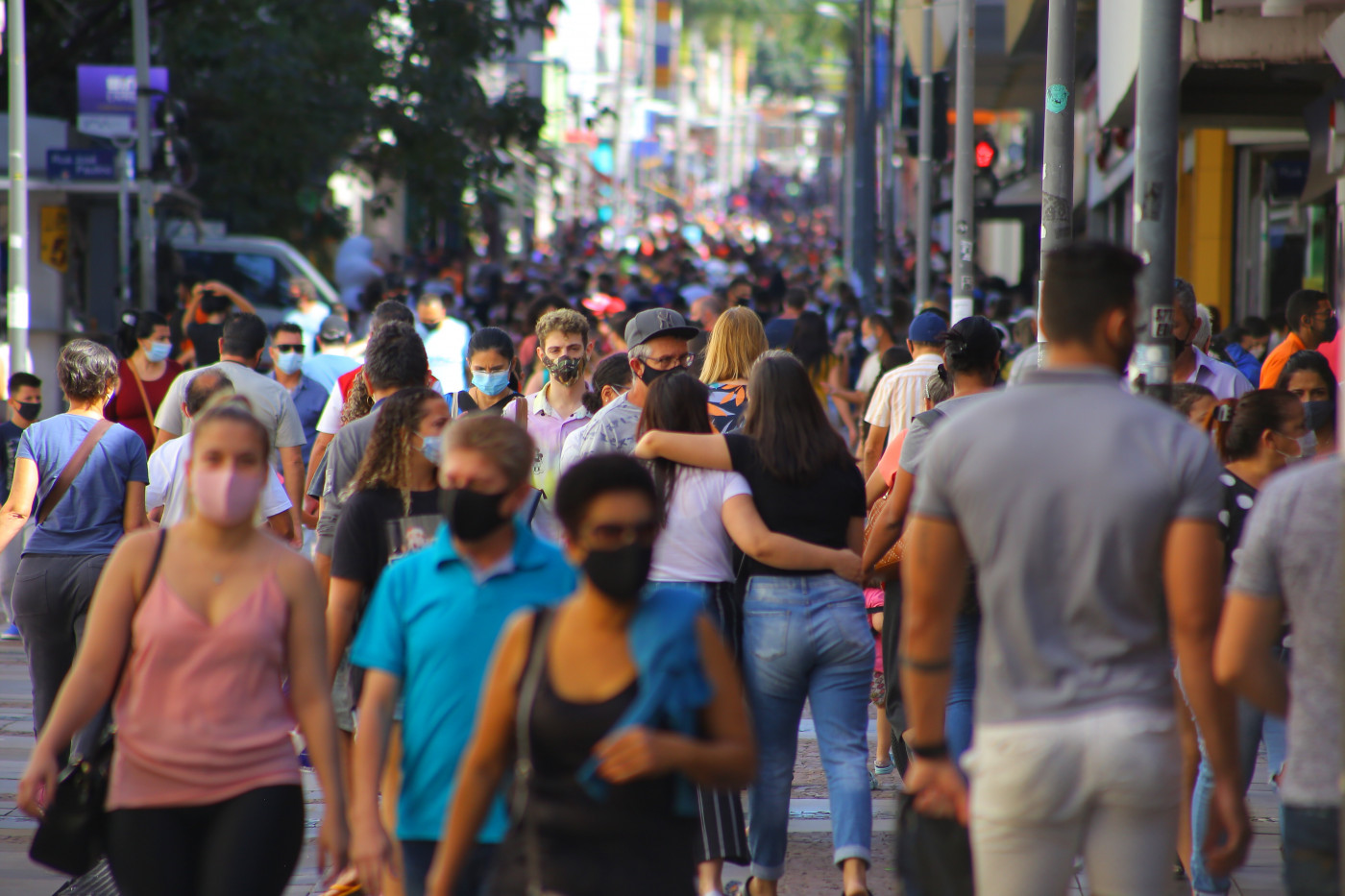 Pessoas andando na rua usando máscara