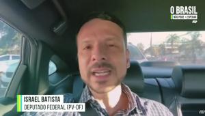 Homem falando para a câmera dentro de um carro. Tem o cabelo bastante curto, bigode e cavanhaque e usa camisa social listrada.