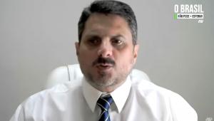 De camisa branca e gravata azul marinho estampada, o senador Marcos do Val, usando bigode e cabelo preto curto, grava depoimento à Jovem Pan