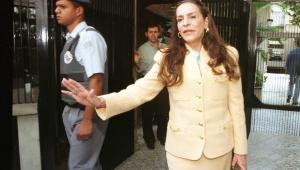 de conjunto amarelo gema, Nicéa Camargo, ex-mulher de celso Pitta, deixa o prédio onde morava na época da foto; um policial militar aparece na imagem