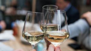 Mãos de três pessoas brindando com três taças pouco cheias de vinho branco