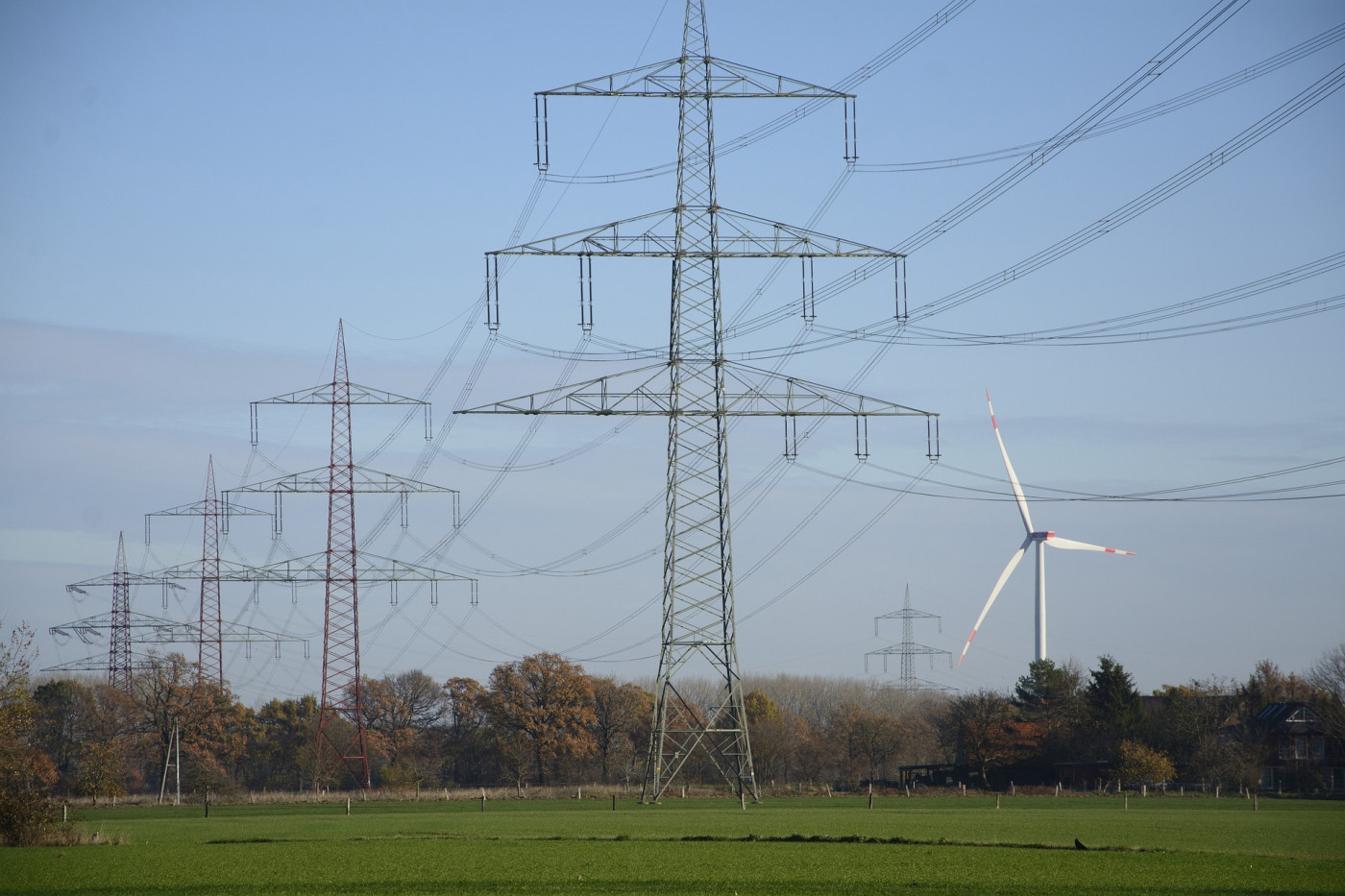 Postes com fios de luz em um cenário de um chão com gramas e céu azul. Do lado, um catavento de geração de energia eólica