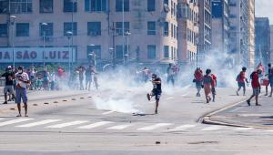 Em uma via esfumaçada devido a uma bomba de gás lacrimogênio, com diversos prédios ao fundo, manifestantes correm da polícia (uma minoria aguarda por ela parada)