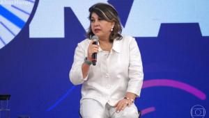 Roberta Miranda com uma camisa e calça branca com um microfone na mão, sentada em um banco, no programa Altas Horas. Mulher branca, de cabelos castanhos com mechas loiras channel