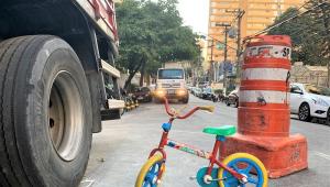 Pequena bicicleta multicolorida está parada na rua bem perto de um cone da CET e de um caminhão