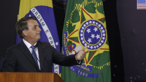 Jair Bolsonaro falando. Ao fundo, bandeiras do Brasil