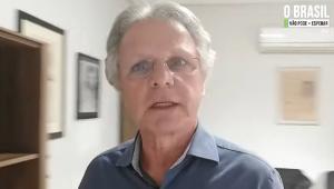 Em pé. de camisa azul, Vanderlei Macris grava um depoimento em um cômodo com paredes brancas e alguns quadrros na parede; le é branco, tem 66 anos e seu cabelo é liso e totalmente grisalho