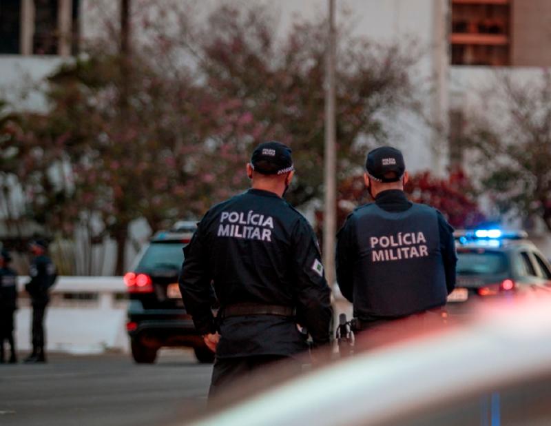 Dois policiais militares olhando para os carros na rua