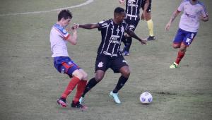 Jô usa o braço esquerdo para proteger a bola de defensor do Bahia, enquanto Gilberto um corintiano (cuja cabeça não aparece observam o lance