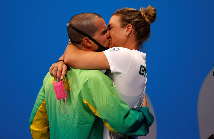 Com uniforme da delegação brasileira em Tóquio, o nadador Bruno Fratus beija sua mulher Michelle Lenhardt, também sua treinadora (ambos são caucasianos)
