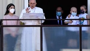 Papa Francisco lendo um texto em varanda de um hospital. Ao lado, duas crianças usando máscaras e um homem de terno atrás delas
