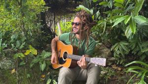 Cantor Gabriel Elias tocando violão em meio à natureza