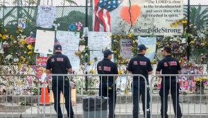 pessoas diante de memorial para vítimas de desabamento em Miami