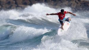 Surfista brasileiro fazendo manobra em Tóqui