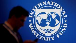 Homem passa em frente ao logo do Fundo Monetário Internacional