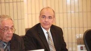 Homem careca usando terno e óculos de grau olhando para a câmera ao lado de outro homem em uma reunião