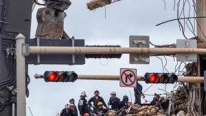 Bombeiros buscando por sobreviventes em escombros de prédio