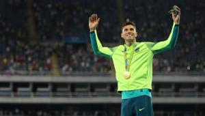 Thiago Braz, do salto com cara, levanta os braços e exibe medalha de ouro no peito no estádio