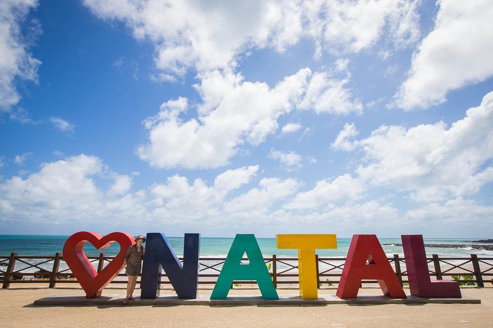 Letreiro com um coração e a palavra Natal, cada letra com uma cor, em frente a uma praia da cidade potiguar