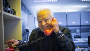 O jornalista Cid Moreira, então com 89 anos, posa sorrindo segurando um telefone rente à orelha