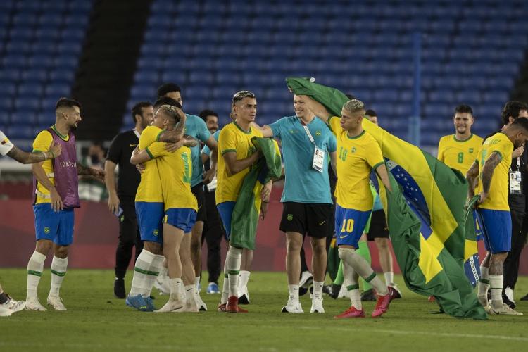 Jogadores da seleção brasileira celebram título em campo; Richarlison carrega uma bandeira do Brasil, que balança em suas costas