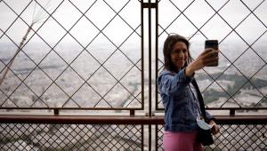 Mulher tirando selfie no topo da torre eiffel