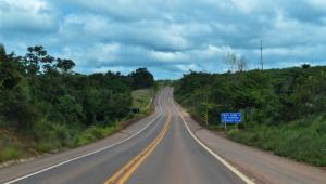 Foto de uma rodovia com uma faixa amarela no meio. Ao fundo céu azul com nuvens e aos lados árvores