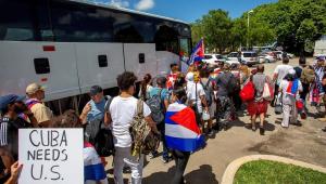 Com bandeiras de Cuba e cartazes, cubanos-americanos formam fila para entrar em ônibus rumo a Washington D.C.