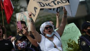 Pessoas protestando, mulher em evidência carregando um papelão escrito 'Abajo la dictadura'