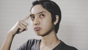 Pessoa com um dedo na cabeça como se estivesse pensando e com uma cara de dúvida. Tem os cabelos pretos curtos