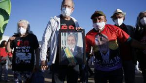 Com uma camiseta preta, calça jeans e jaqueta cinza clara, José Dirceu segura quadro de Lula ao lado de militantes petistas durante protesto contra Jair Bolsonaro em Brasília