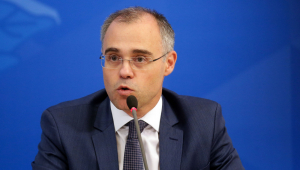 Homem de terno gravata e oculos falando em microfone