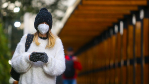 Mulher usa blusa de lã branca, touca e luvas pretas para se proteger contra o frio