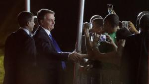 De terno azul marinho, Jair Bolsonaro conversa com apoiadores, que estão no cercadinho do Palácio do Alvorada; percebe-se que está de noite