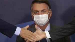 De traje social e máscara, presidente Jair Bolsonaro tem olhar perdido enquanto duas pessoas fazer cumprimento com as mãos à sua frente