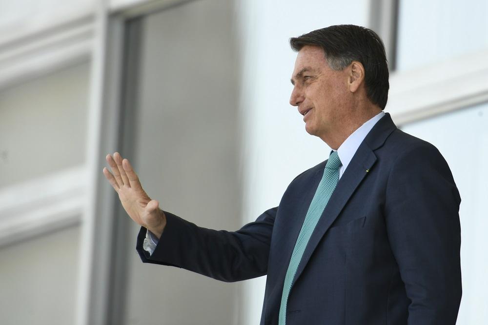 De traje social, o presidente Jair Bolsonaro acena