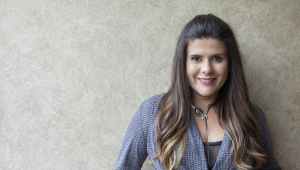 Mulher apoiada em parede cinza sorrindo para a câmera. Tem cabelos castanhos e lisos longos, usa um colar e um casaco de malha azul, com uma blusa roxa por baixo