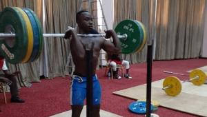 Homem levantando um peso grande. Ele é negro e usa bermuda azul. Atrás, tatames e pesos menores no chão