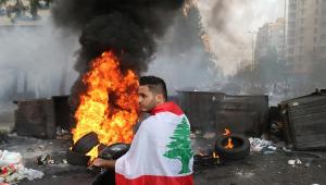 homem na frente de fogo durante protesto