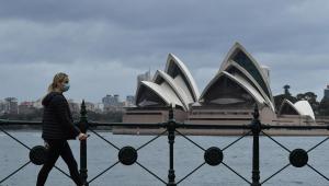 Mulher usando máscara caminha em frente ao monumento Opera House, na Austrália.