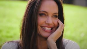 A atriz Angelina Jolie sorrindo com a mão no queixo