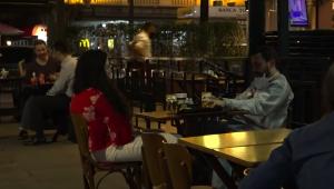 Pessoas sentadas em mesas de restaurante na calçada em São Paulo