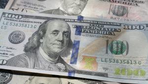 Imagem mostra três notas de dólares, uma de 100 no meio de duas de 50, colocada sobreposta às outras