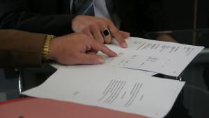 Duas mãos em cima de um papel apontando para algo