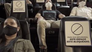 Pessoas em uma sala de cinema usando máscara